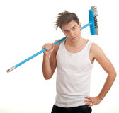 Serious young man with sweeping brush Stock Photography