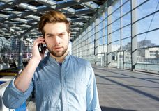 Serious young man talking on mobile phone inside building Royalty Free Stock Image