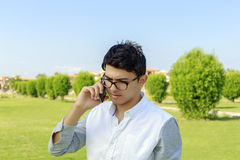 Serious young man talking on phone. Stock Photos