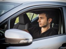 Serious young man or teenager driving car Stock Images