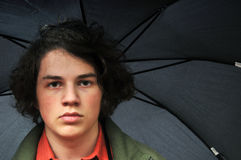 Serious young man under black umbrella stock photos