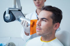 Serious young man undergoing dental checkup Royalty Free Stock Photos