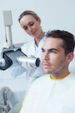 Serious young man undergoing dental checkup Stock Images