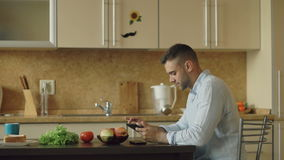Serious young man using digital tablet computer sitting in the kitchen while have breakfast in the morning stock video