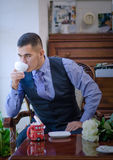 The serious young man in a vest, a tie and with a beard. Sits on a chair at a window and has tea or coffee Royalty Free Stock Photos