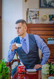 The serious young man in a vest, a tie and with a beard. Sits on a chair at a window and has tea or coffee Stock Photo