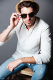 Serious young man in white shirt, jeans, sunglasses and hat. Fashion portrait of serious young man in white shirt, jeans, sunglasses and hat over grey background Royalty Free Stock Photography