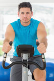 Serious young man working out at spinning class Royalty Free Stock Photography