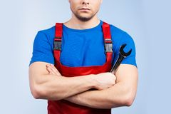 Serious young mechanic in red overall on blue background. Royalty Free Stock Image