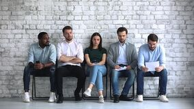 Serious young mixed race job applicants feeling nervous before interview.
