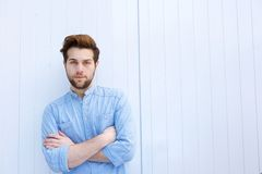 Serious young modern man standing with arms crossed Stock Photo