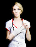Serious young nurse removing her latex gloves Royalty Free Stock Photos