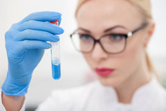 Serious young scientist is doing her research. Cheerful female researcher is making experiments in laboratory. The woman is holding a flask of blue liquid and Stock Photography
