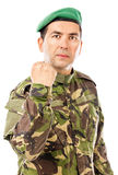 Serious young soldier with arm raised showing his fist Royalty Free Stock Photos