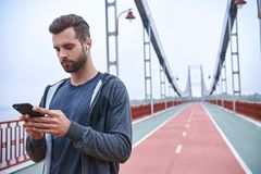 Serious young sportsman using fitness tracker and smartphone outdoors. Serious young sportsman using fitness tracker and smartphone royalty free stock photos