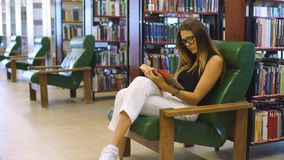 Serious young student reading a book in a library. Girl reading book on green chair stock footage