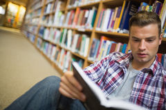 Serious young student sitting on library floor reading book Royalty Free Stock Photos