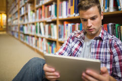 Serious young student sitting on library floor using tablet. In college Royalty Free Stock Photography