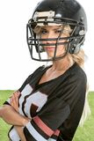 serious young woman in american football uniform looking at camera with crossed arms