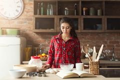 Serious young woman baking in loft kitchen. Serious young woman baking pie in loft kitchen at home, using book with recipe. Mockup, copy space Royalty Free Stock Photo