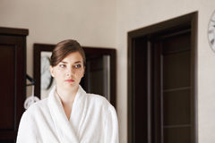 Serious young woman in bathrobe Stock Image