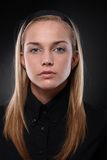 Serious young woman in black Stock Images