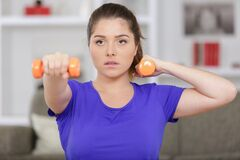 Serious young woman doing dumbbells