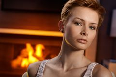 Serious young woman by fireplace Royalty Free Stock Photos