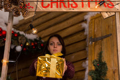 Serious Young Woman Giving a Golden Gift Box Royalty Free Stock Image