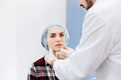 Serious young woman having an appointment with a plastic surgeon. I want to be beautiful. Serious young nice women wearing a cap and sitting in front of her Stock Photo