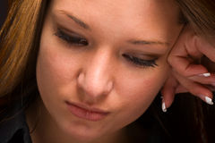 Serious young woman looking down. Close-up of attractive young woman looking down with serious expression Stock Image