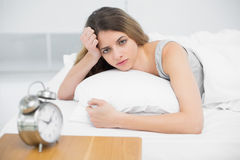 Serious young woman lying on her bed under the cover Royalty Free Stock Image