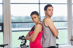 Serious young woman and man standing back to back in gym Royalty Free Stock Photo