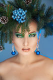 Serious young woman with nice makeup and xmas tree-wreath on hea Stock Photo