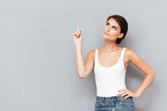 Serious young woman pointing finger up Royalty Free Stock Photos