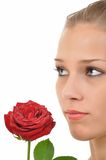 Serious young woman with red rose. Serious young woman with a rose full of water drops Royalty Free Stock Image