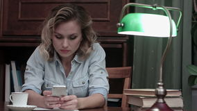Serious young woman sitting at her workplace and typing an message on her phone stock video