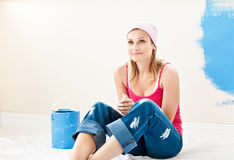 Serious young woman sitting in the room she paints Stock Photo