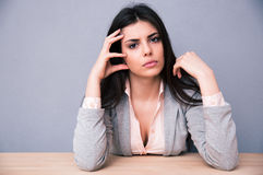 Serious young woman sitting at the table Stock Images