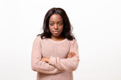 Serious young woman standing with folded arms. Serious young African American woman standing with folded arms staring at the camera with a calm emotionless stock photo