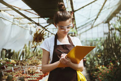 Serious young woman standing in greenhouse holding clipboard Royalty Free Stock Photography