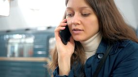 Serious young woman talking on the phone and gets on the train in the subway stock footage