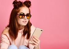 Serious young woman in trendy eyewear concentrated on information looking at phone stock image