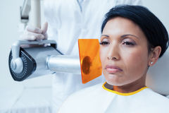 Serious young woman undergoing dental checkup Royalty Free Stock Image