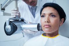 Serious young woman undergoing dental checkup Royalty Free Stock Images