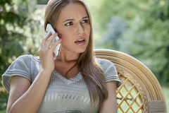 Serious young woman using cell phone on chair in park Royalty Free Stock Photos