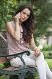Serious young woman using cell phone on park bench Stock Photography