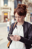 Serious Young Woman Using Phone While Walking Royalty Free Stock Photos