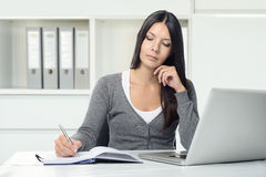 Serious young woman working at a desk. Serious attractive young woman working at a desk with her laptop computer writing notes in a notebook conceptual of a royalty free stock images