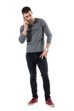 Serious young worried casual man talk on the phone looking down. Full body length portrait isolated over white studio background Stock Image